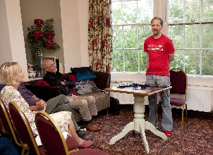 Poet Giles L. Turnbull at Poetry in Presteigne, wearing a red tshirt bearing the slogan The Future is Accessible