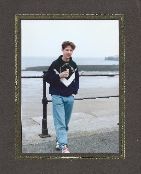 Photo of Giles L. Turnbull standing on the seafront at Mumbles, Swansea in 1991/92. Giles is wearing a Swansea University jumper.
