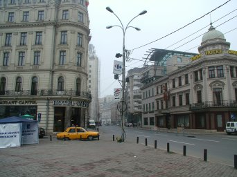 Calea Victoriei. In the photo can be seen a parked yellow taxi and further up the street is a sign for Pizza Hut.